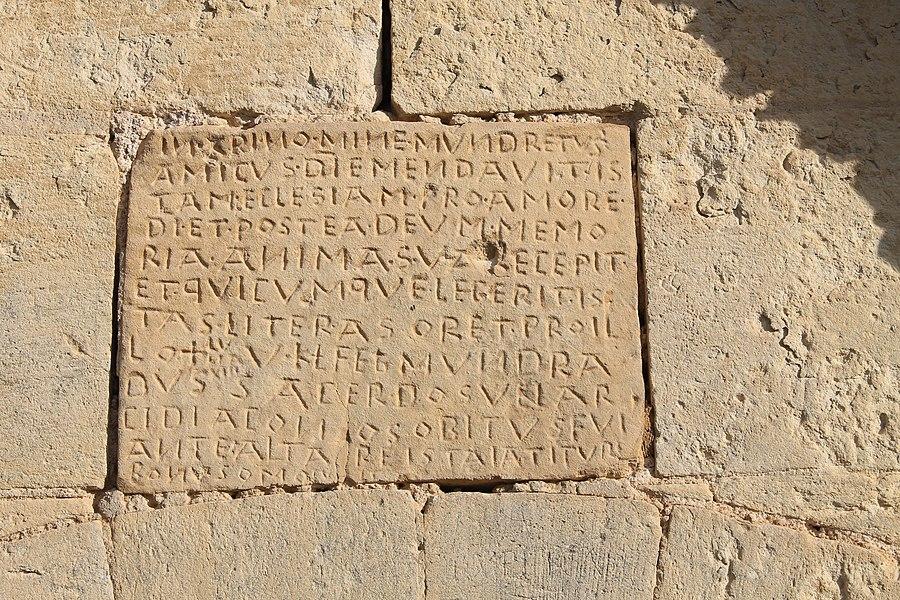 """Epitaphe dite """"Pierre à Mundret"""" concernant le curé fondateur: l'archidiacre Mundretus. Ecrite en latin, cette inscription funéraire placée sur la façade sud de l'église Saint-Denis daterait du 10 ème siècle ou avant. Mondrainville (Calvados)"""