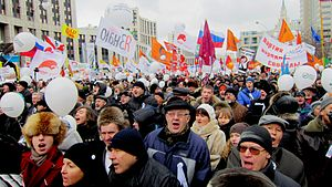 alt = A crowd of enthusiastic protesters on Academician Sakharov Avenue, Moscow. Many balloons, posters, and flags. The protesters are bundled up on a cold overcast Winter day.