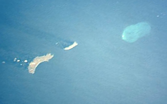 Motu One (Marquesas Islands) - Northwestern Marquesas Islands. Motu One and its lagoon are the pale blue oval shape in the upper right. Image courtesy of Johnson Space Center.