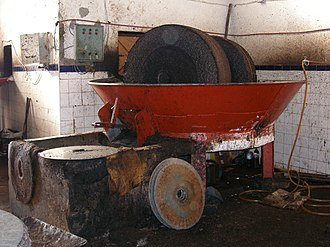 Olive oil extraction - Grinder with two millstones and in the foreground several fiber disks