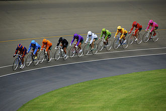 Keirin - During a race at Omiya Velodrome in Saitama, the nine racers form a line behind the pacer as they go around a corner.