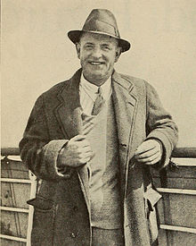middle-aged man in overcoat and trilby hat smiling cheerfully towards the camera
