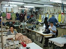 People at sewing machines in a small garment factory