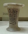Photograph of a small white vase with black hieroglyphs on it