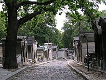 A cobbled street stretches out from the foreground and bends to the left. The street is lined with above-ground tombs, and a number of trees appear in the background.