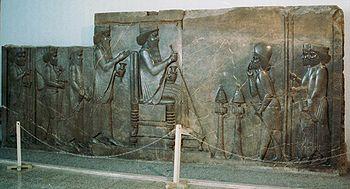 Sovrano persiano (al centro) e un suddito del Gran Re mentre effettua la proskýnesis (a destra). Secondo un'altra lettura si tratterebbe invece di un'udienza concessa a un alleato che, infatti, non si genuflette.