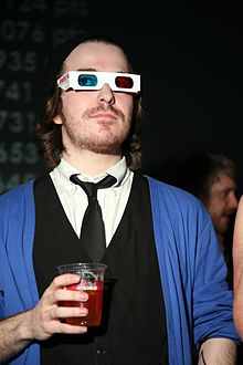 Fish wearing anaglyph (3D) glasses, a black tie and vest, and blue cardigan while holding a red drink at the GAMMA 3D 2008 video game event