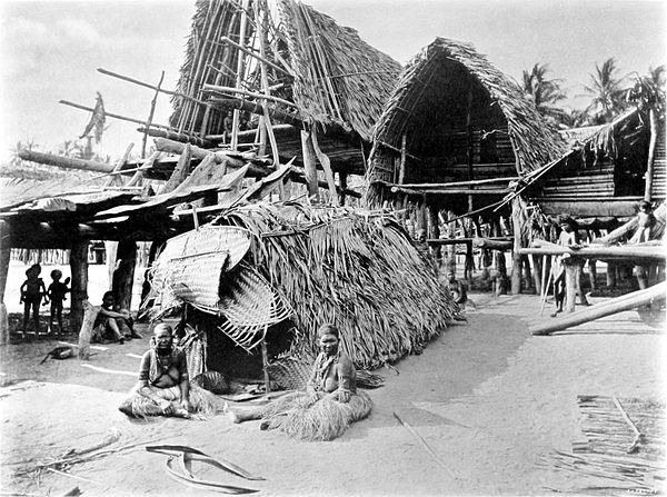 Black and white photograph of a village.  In the foreground is a small, thatched tent-like, A-frame building.  Two people sit outside the front entrance.
