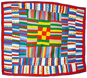 The Quilts of Gee's Bend - Lucy Mingo of Gee's Bend, Alabama made this spectacular pieced quilt in 1979. It includes a nine-patch center block surrounded by pieced strips. Collection of Bill Volckening, Portland, Oregon.