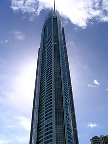 The tall, thin building rises into a blue sky flecked with a few clouds.