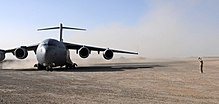 Colour photo of a grey military aircraft on a dusty airstrip. A person is standing to the right of the aircraft.