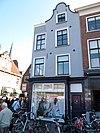 foto van Ondiep pand op de hoek van het verbindingsstraatje tussen Markt en O. Langendijk. Gepleisterde voorgevel, waarvan het rechterdeel hoger is opgehaald en beëindigd als klokgevel onder rollaag
