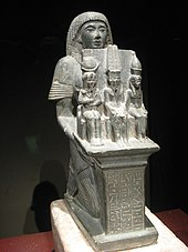 Statue of a man seated and holding three smaller statues of gods.