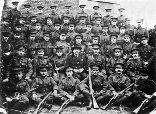 A formative photograph of soldiers in First World War British uniforms, standing and sitting in six rows. A gentleman in civilian clothes sits in the centre of the second row from the front.