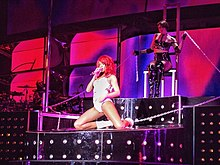 A woman with red hair wearing a white PVC body suit is performing on a raise platform. She is singing into a microphone and is handcuffed to the stage.