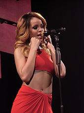 Ženy v červených šatech zpívající do zlatého mikrofonu