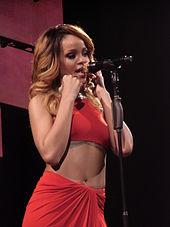 O femeie cu o rochie roșie cântând într-un microfon auriu