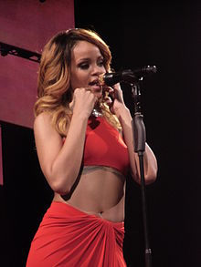 A dark blonde woman singing into a golden microphone