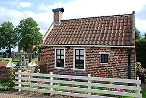 Rottum, Groningen - A tiny house, Jan Boer's bust, and the church in the background