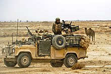 Desert-coloured Land Rover with mounted machine gun