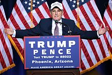 Giuliani with his arms outstretched, standing a podium with a banner for the Trump/Pence ticket