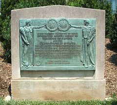Bronze plaque containing two human figures holding the seal of the United States and the coat of arms of Great Britain with a description of the treaty in between them.