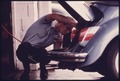 SERVICE STATION MECHANIC ADJUSTS THE ENGINE FOR A YOUNG WOMAN WHOSE VEHICLE HAD FAILED THE EMISSIONS TEST AT AN AUTO... - NARA - 557925.tif