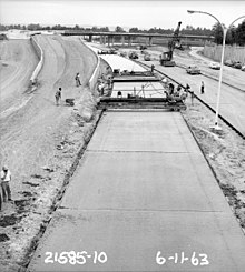 A black and white photograph of a concrete road in the middle of paving. Piles of dirt, forming a ramp, can be seen in the background.