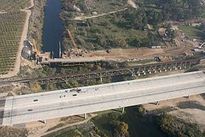 California State Route 99 - CA 99 crosses the San Joaquin River at the northern border of Fresno.  The early stages of construction of California High-Speed Rail's San Joaquin River Viaduct, as well as the existing Union Pacific Railroad bridge, are also visible.