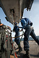 Seaman Samuel Soto, left, attaches a cargo pendant to an MH-60R Sea Hawk helicopter while Seaman Edward Johnson holds on to him as a safety observer during a vertical replenishment aboard the guided-missile cru 121214-N-LV331-598.jpg