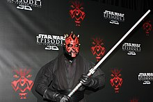 homme maquill en rouge et noir avec des vtements noirs et un sabre