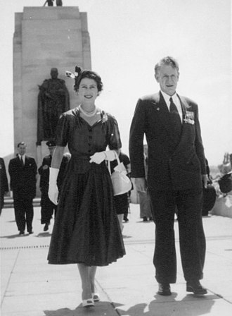 1945–60 in Western fashion - Queen Elizabeth II and her then-Minister for Veterans' Affairs in Australia, 1954. The Queen's summer suit features a fitted short-sleeved jacket with a peplum and a full skirt. The minister wears a double-breasted suit.