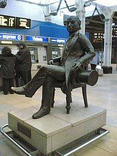 A black statue of a seated man holding a top hat.