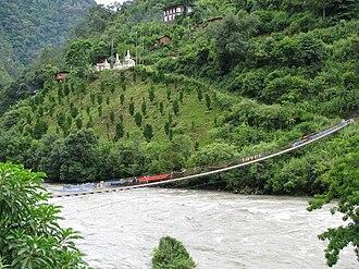 Lhuntse Dzong - Suspension bridge across the Kuri Chhu river on the way to Chortens and the Dzong