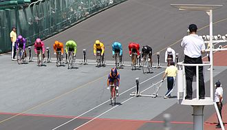 Keirin - Start of a race at Tachikawa Velodrome in Tokyo. Riders start from the blocks and pace up to speed behind the pacer, wearing purple and orange. A referee observes the start in the tower to the right.