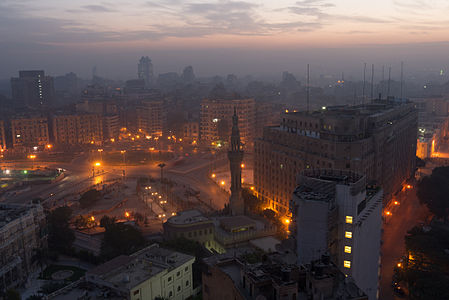 Tahrir Square, Cairo, in the early morning. The street lights are glowing like lava, while dawn is painting a orange-reddish band on the horizon.