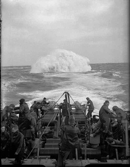 Depth charges detonate astern of the sloop HMS Starling. She participated in the sinking of 14 U-boats throughout the war The Battle of the Atlantic 1939-1945 A22031.jpg