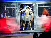 "On the revamped show, ""LoveGame"" was performed (left) decked in a nun's habit, and dancing inside a subway coach. During ""Telephone"", Gaga danced to the choreography seen in the song's video (right)."