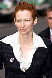Женщина с зачесанными назад волосами в костюме смотрит налево