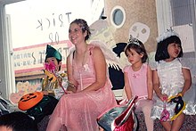 A woman dressed as a fairy surrounded by children