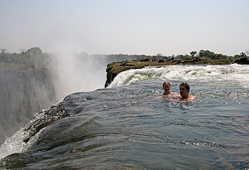 Tourists swimming at Victoria Falls