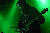 A bearded man playing guitar on stage; the picture is tinted green