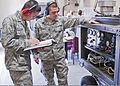 U.S. Air Force Airman Michael Hoy, left, and Senior Airman Joseph Szymanski, both with the 361st Training Squadron, check their instruction manual for a gas turbine generator to troubleshoot an electrical 110608-F-NS900-016.jpg