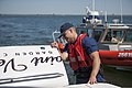 U.S. Coast Guard Petty Officer 2nd Class Eric Ryan, with Coast Guard Station Fire Island, inspects the engine and ensures that enough life jackets are on board during a safety boarding near Fire Island, N.Y 130527-G-EQ432-564.jpg