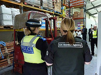 Police community support officer - A PCSO (left) with a UK Border Agency (UKBA) officer (right) at a customs raid. Note the distinctive badging on the back of the PCSOs body armour as well the distinctive hat band (the most commonly used) and blue epaulettes (the most commonly used)