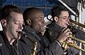 US Navy 060324-N-9851B-003 Musician 2nd Class Rick Devoe, Musician 3rd Class Antonio Rice, and Musician 2nd Class Adam Stuble perform on the pier with the 7th Fleet rock band.jpg
