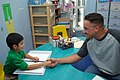 US Navy 070721-N-6645H-071 Cryptologic Technician Technical 1st Class Wayne Good greets a child at Alia School for Early Intervention.jpg
