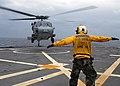 US Navy 080212-N-5067K-280 Aviation Boatswain's Mate (Fuels) Airman, Lowel A. Shorey III directs an MH-60S Seahawk during deck landing qualifications on the flight deck aboard the amphibious transport dock USS Juneau (LPD 10).jpg