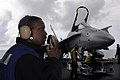 US Navy 090615-N-2475A-010 Aviation Boatswain's Mate (Handling) Airman Kelsey Gifford, from Augusta, Ga., communicates with hangar deck control while hangar bay personnel transfer a F-A-18C Hornet.jpg