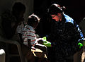 US Navy 100125-N-4774B-162 Culinary Specialist 3rd Class Ruth Dobson, from the guided-missile cruiser USS Bunker Hill (CG 52), assists with medical care of a Haitian girl as part of continuing relief efforts.jpg